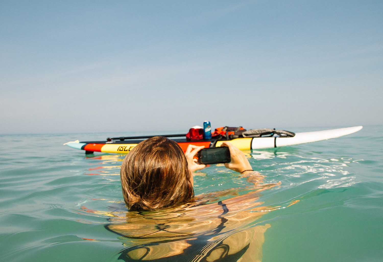 Woman using phone to take photo in sea